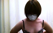 Short-haired Asian woman changes clothes while wearing a ma